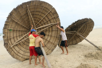 People remove beach cabanas ahead of typhoon Molave in Danang, Vietnam. The storm is expected the hit tourism areas hard.