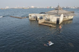 Children swim next to an abandoned mosque in Jakarta.