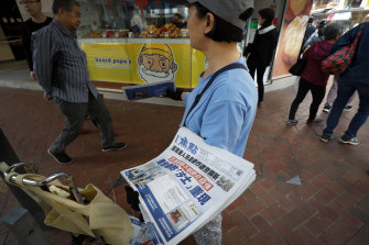 A vendor gives out copies of newspaper with a headline about the coronavirus in Hong Kong.