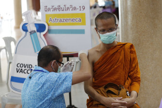 A Thai health worker administers a dose of the AstraZeneca COVID-19 vaccine to a Buddhist monk.