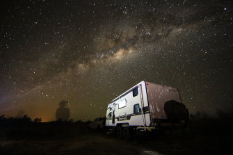 """Simon and Liz Bailey's caravan under the starry outback sky, with an outline of Simon on the horizon. The family are on the road """"full-time and indefinitely""""."""