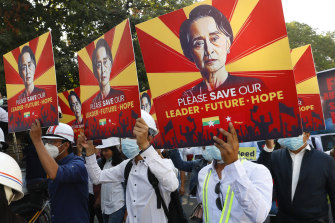 Engineers hold posters with an image of deposed Myanmar leader Aung San Suu Kyi as they hold an anti-coup protest march in Mandalay.