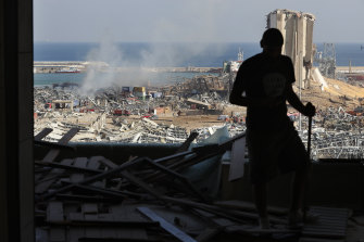 A man stands in a damaged apartment as he looks out at the scene of a massive explosion.