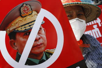 A protester holds a placard with the face of Myanmar's commander in chief, Senior General Min Aung Hlaing during a rally in Mandalay.