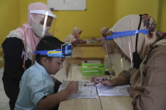 Teachers and students wear protective gear at a Koran educational facility at on the outskirts of Jakarta.
