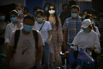 People wearing face masks wait to cross an intersection in the CBD in Beijing.