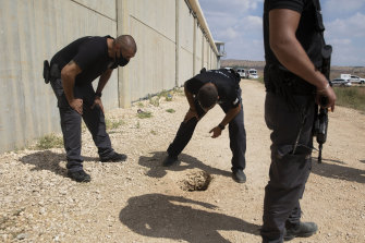 Police officers examine a second hole just outside the walls of the prison.