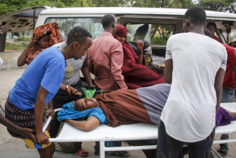 Medical workers and other Somalis help a woman, who was wounded when a powerful car bomb blew off the security gates to the Elite Hotel, as she arrives at a hospital in Mogadishu.