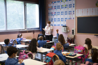 Children and their teacher wear protective masks inside an elementary school
