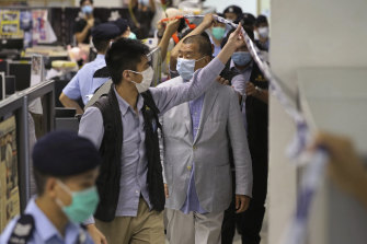 Jimmy Lai is escorted by police inside the Apple Daily newspaper headquarters.