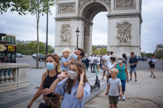 A family walks along on the Champs-Elysees in Paris.