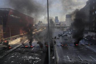 Black smoke rises from burning tires set by protesters to block a main highway north of Beirut.