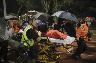 Medical workers move an injured student following clashes with police at the Chinese University in Hong Kong.
