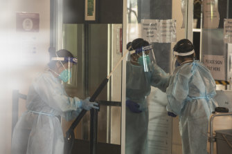 Cleaners wearing full PPE disinfect the Holiday Inn Hotel.