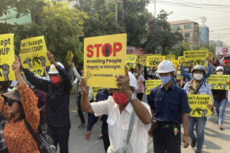 Anti-coup protesters display signs and shout slogans as they protest against the military coup in Mandalay, Myanmar, on Monday.