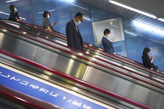 People using escalators in Tokyo, where restrictions are not lifted.