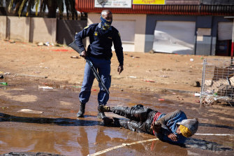 South African police force suspected looters to lie down and roll in muddy water after apprehending them in Soweto, Johannesburg.