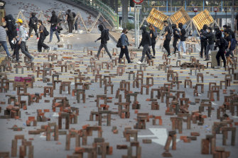 Protesters walk past barricades of bricks on a road near the Hong Kong Polytechnic University in Hong Kong.