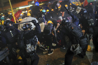 Police with batons charge protesters.