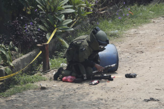 A member of the police bomb disposal squad inspects a suspicious package found inside a garbage, that they later destroyed, in Bekasi on the outskirts of Jakarta, Indonesia, on Monday.