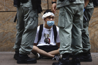 Riot police guard a protester as a second reading of a controversial national anthem law takes place in Hong Kong on Wednesday.