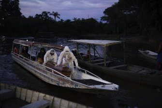 Funeral workers transport an 86-year-old woman's coffin by boat after she died of suspected COVID-19 near Manaus, Brazil.