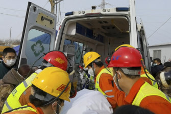 Rescuers carry a miner who was trapped in a gold mine.