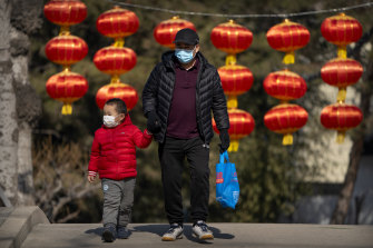 A man and child walk past lanterns at a public park in Beijing. While Beijing ended its controversial one-child policy in 2017, it had not yet published new family size limits.