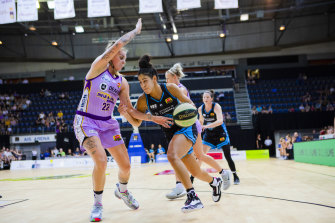 Canberra's Kia Nurse (right) drives past Cayla George of the Melbourne Boomers in Sunday's victory.