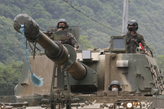 South Korean army soldiers ride a K-9 self-propelled howitzer during the annual exercise in Paju, South Korea, near the border with North Korea, on Tuesday, amid threats from the North.