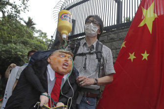 Pro-China supporters hold the effigy of US President Donald Trump and a Chinese national flag outside the US Consulate during a protest in Hong Kong on Saturday.