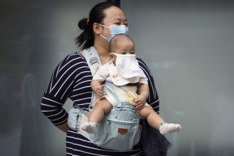A woman and baby wear masks to help protect against the coronavirus in Beijing.