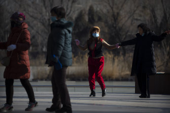 People wearing face masks to curb the spread of the coronavirus dance at a public park in Beijing, as parts of the neighbouring Hebei province have been classified a coronavirus high danger zone.