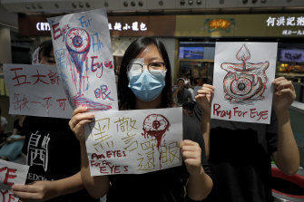 After a girl is hit in the eye with a police beanbag round, protesters wear patches in solidarity as they occupy the city's airport in August.