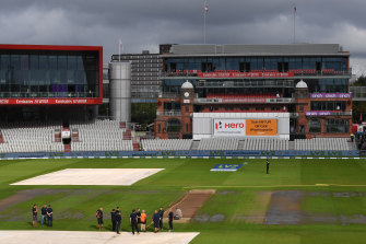 Old Trafford staff gather on the field after the cancellation of the fifth Test between England and India.