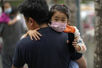 A man carries a child kindergarten in Beijing this week.