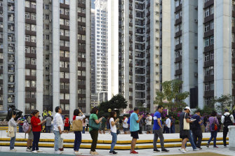 Voters line up outside a polling place in Hong Kong on Sunday.