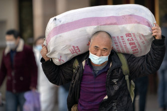 A traveller wearing a face mask to protect against the spread of the coronavirus carries his luggage at the Beijing Railway Station on Thursday.