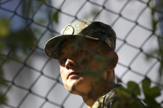 A soldier from China's People's Liberation Army (PLA) watches a confrontation between police and protesters at the Hong Kong Polytechnic University in November.