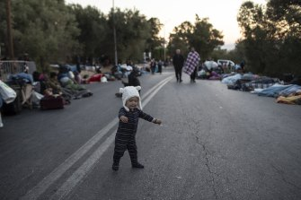 A boy tries to stand as migrants sleep on the road near the Moria refugee camp on the island of Lesbos, Greece, on Thursday.