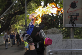 A protester prepares to throw a molotov cocktail at the Tsim She Tsui police station during Sunday's protests.