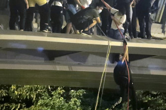 Protesters use a rope to lower themselves from a pedestrian bridge to waiting motorbikes.