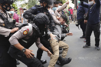 Police officers scuffle with an Afghan refugee during a rally outside the building that houses the UNHCR representative office in Jakarta, Indonesia, on Tuesday, August 24, 2021.