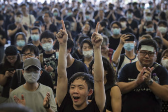Protesters cheer as they listen to a speech by pro-democracy activist Joshua Wong.
