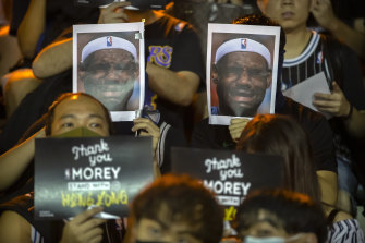 Demonstrators hold up photos of LeBron James grimacing during a rally in Hong Kong.