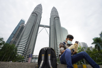 A man looks at his mobile phone in front of Twin Towers in Kuala Lumpur, Malaysia. Huawei is tipped as the frontrunner to build the country's 5G network.