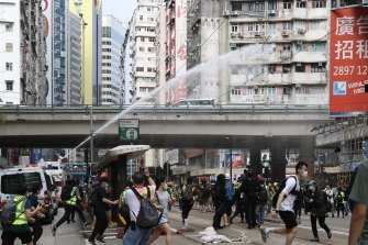 A police water cannon sprays water as journalists and demonstrators run during a protest against a planned national security law in Hong Kong, China, on Sunday.