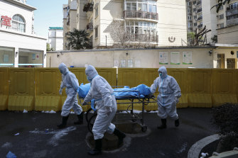 Medical workers move a person who died from COVID-19 at a hospital in Wuhan in Febuary 2020, at the beginning of the pandemic.