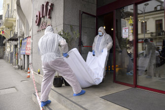 Forensic workers carry the body of Gholamreza Mansouri from a hotel in  Bucharest, Romania