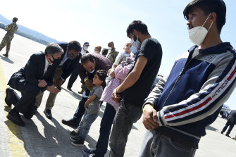 Secretary of State Antony Blinken meets with an Afghan refugee family outside Hangar 5 for evacuation operations at Ramstein Air Base Germany.